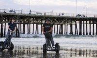 vozítka segway na pláži pod mostem